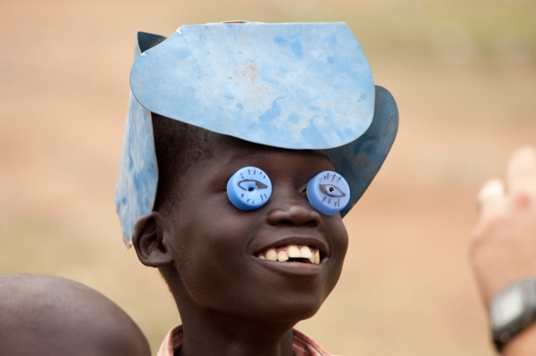 Making a mask out of bottle tops and an engine fan in South Sudan