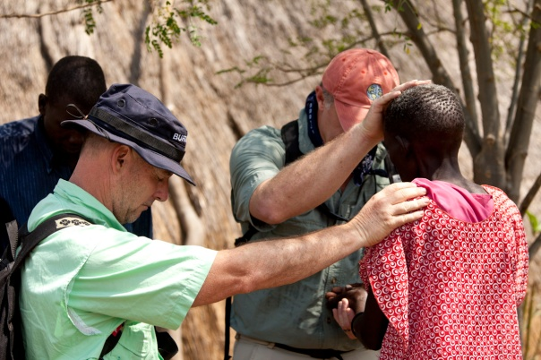 Missionaries pray for a sick woman in South Sudan.