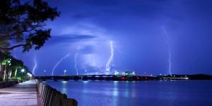 Lighting striking over bridge and water