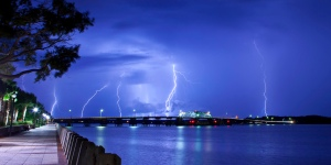 Lighting striking over bridge and water