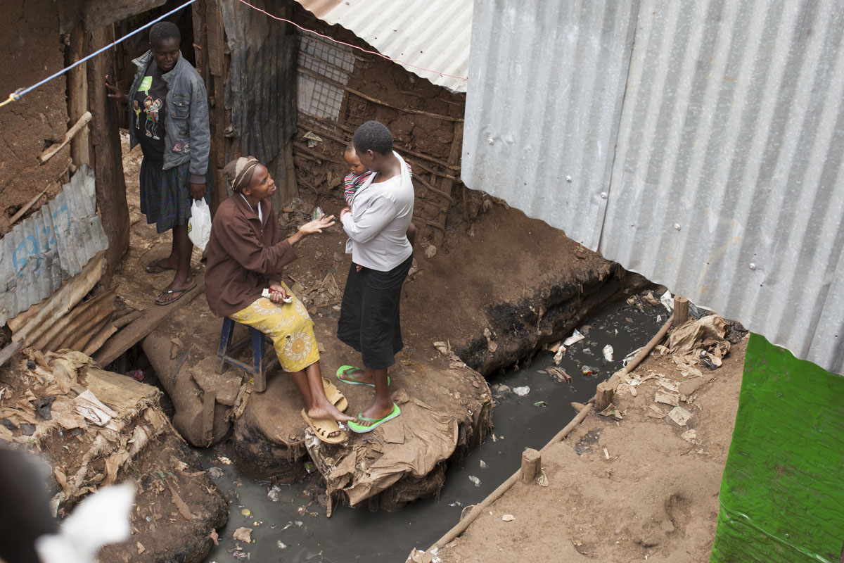 A woman next to open sewage in Kibera, Kenya