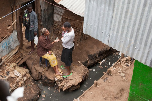 A woman next to open sewage in Kibera, Kenya