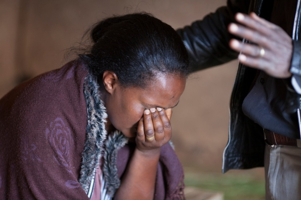 A woman being prayed for in the medical clinic.