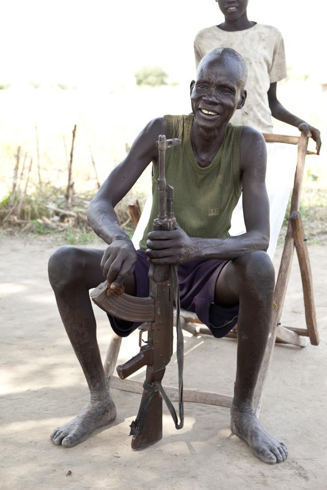A South Sudanese man cleans his gun.