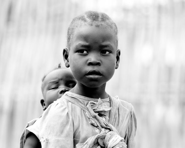 A little girl carries her sister in South Sudan
