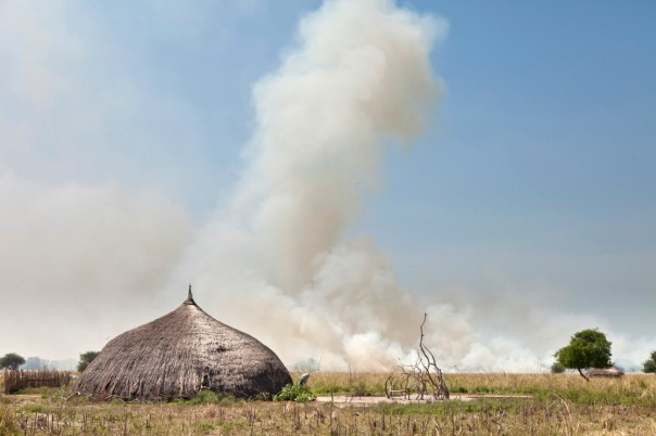 village with grassfire in background, South Sudan