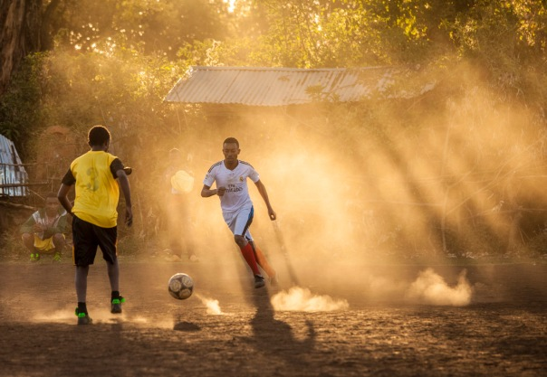 Ethiopian athletes playing football (soccer) at dawn.