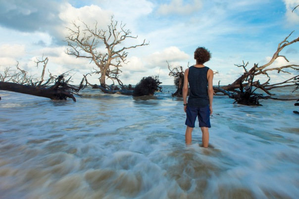 time exposure of young man standing in flowing water looking at dead flooded trees