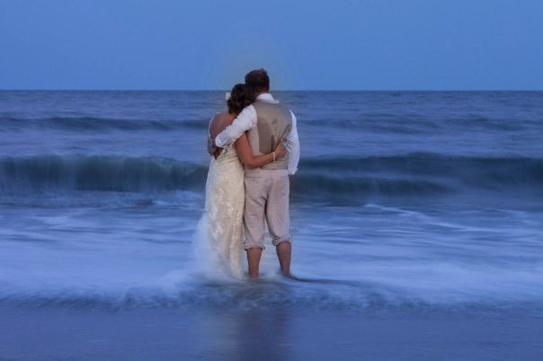 Time lapse of the waves rolling in past the bride and groom.