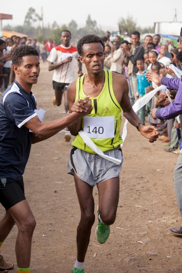 An Ethiopian runner crosses the finish line, utterly spent.